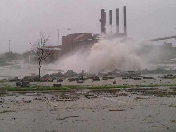 NewsChannel5 photo of large waves crashing against shore in foreground, smokestacks in background