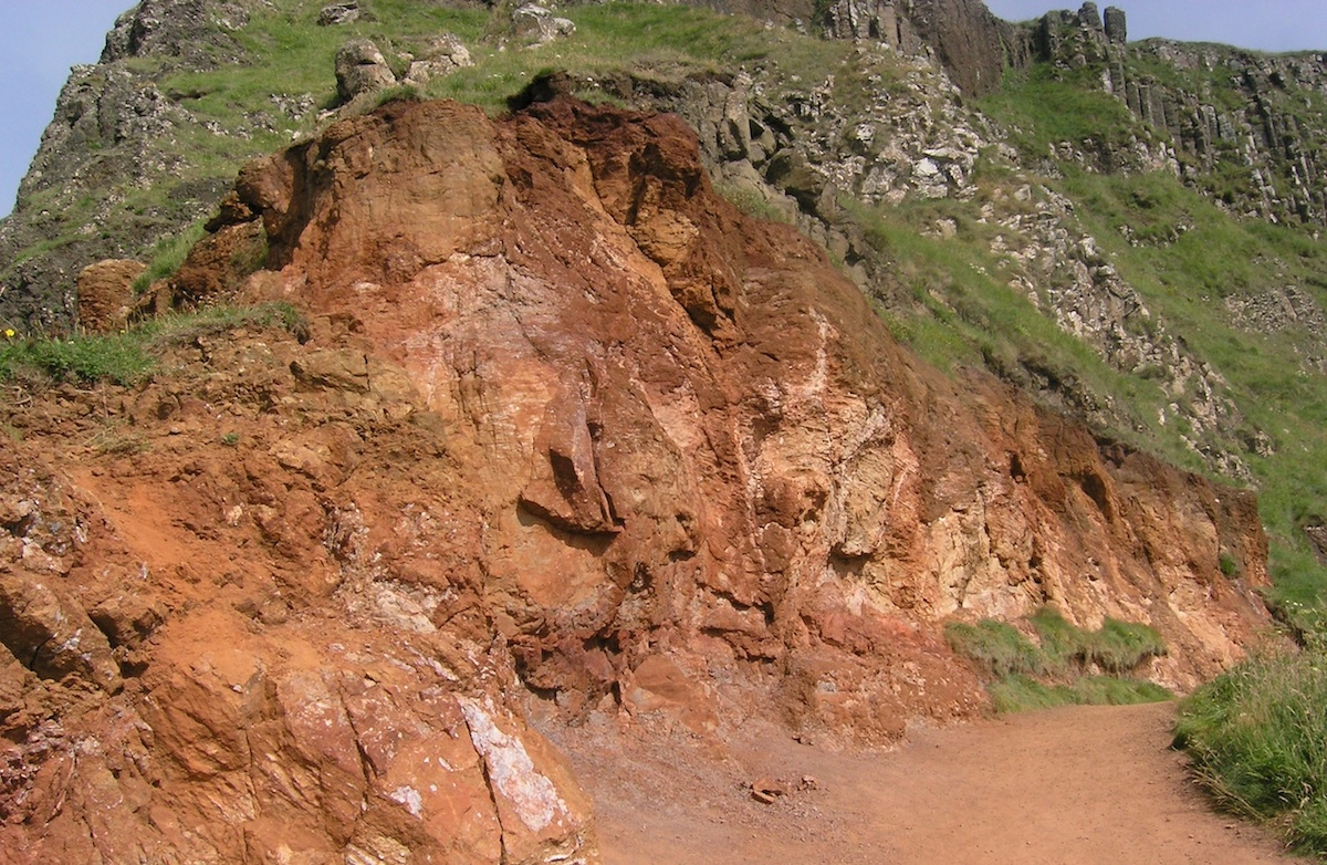 A close-up of the laterite horizon in the cliffs above the Giant's causeway, formed by intense weathering of the top of a lava flow before the next eruption.  Photo: Chris Rowan, 2013