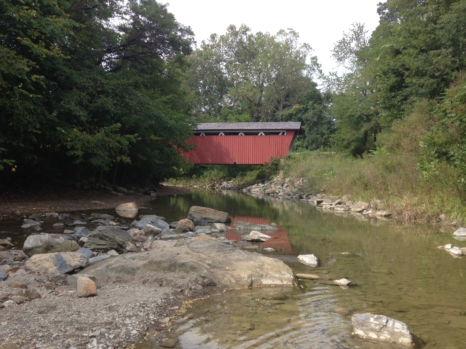 rocks and water in foreground, red covered bridge in background.