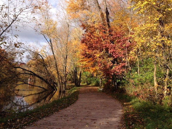 pathway in center, river to left, colorful trees to right
