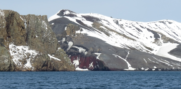 Looking from the caldera back at Neptune's Bellows. On the left are syn-caldera rocks (buff). On the right are post-caldera volcanic products (red and gray). Photo by A. Jefferson.