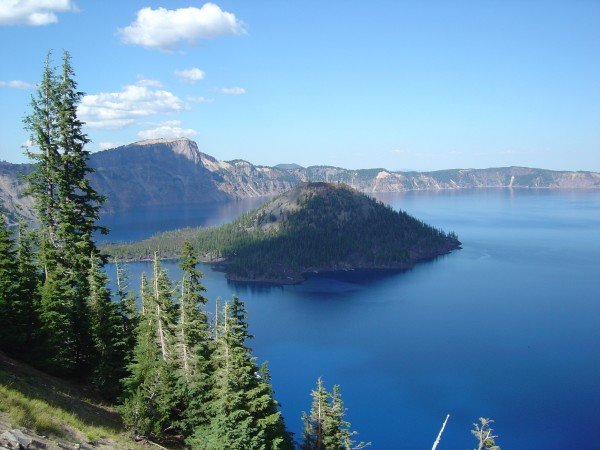 Spectacularly blue lake and sky with cinder cone rising in the center. trees in foreground.