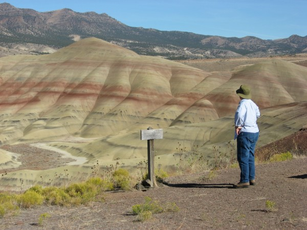 Red and white striped badlands. Person in foreground at right.