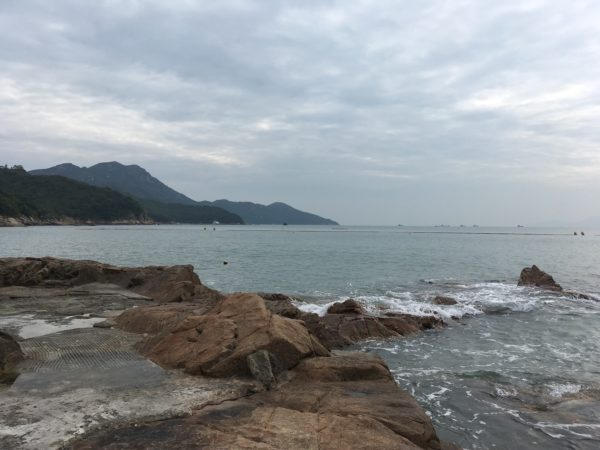 Lamma Island in Hong Kong. A volcanic rock jetty in the foreground, and a forested hilly shore.