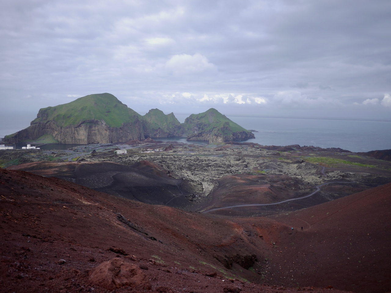A lava flow viewed from its source volcanic cone, together with the small town it almost engulfed in 1973.