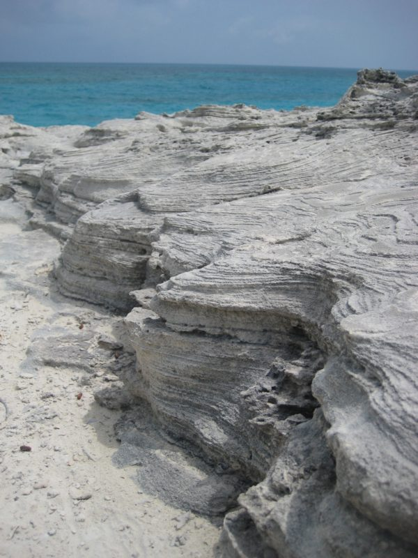 Off-white and grey layers of thinly bedded carbonates on a Bahamas beach