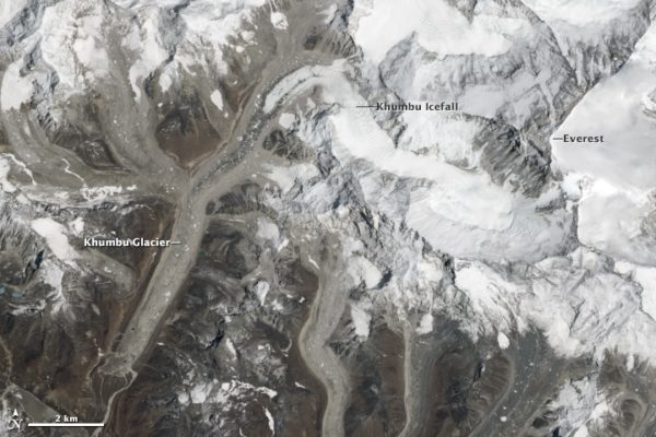 Satellite view of Mount Everest and the surrounding peaks. The summits are covered with bright white snow. The icy glaciers in the valleys between the peaks are a dirty grey colour, covered by debris weathered from the slopes above them.
