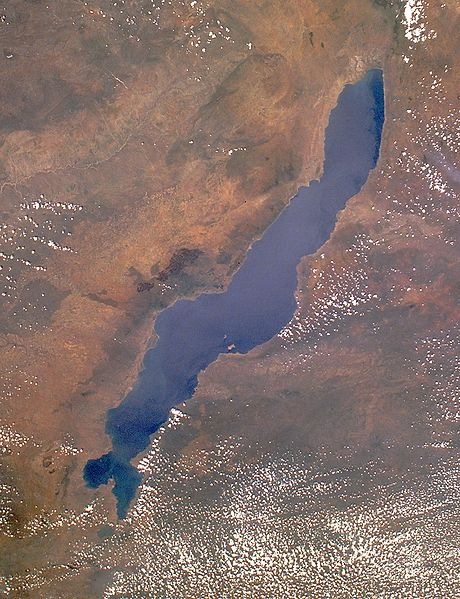 Long narrow blue lake with surrounding brown landscape and scattered white clouds