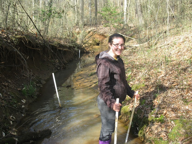 Woman in stream with PVC pipes (piezometers)