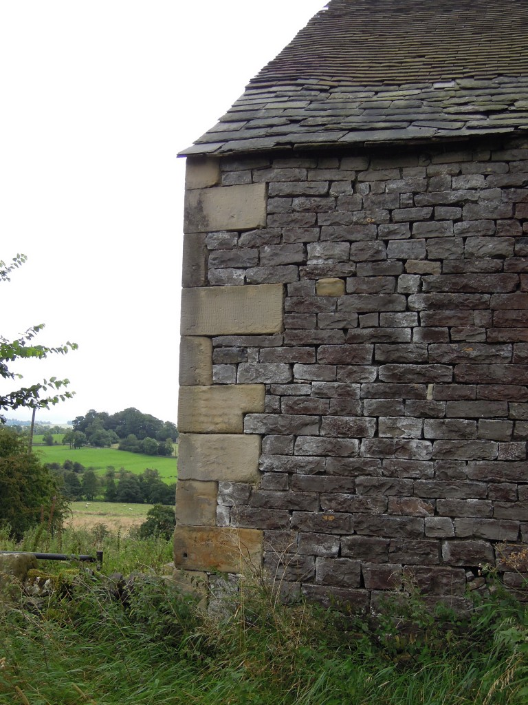 Farm building showing sandstone corners and limestone fill. near Ecton